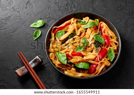 Thai Drunken Noodles or Pad Kee Mao in black bowl at dark slate background. Drunken Noodles is thai cuisine dish with Rice Noodles, Chicken meat, Basil, sauces and vegetables. Thai Food. Copy space #1655549911