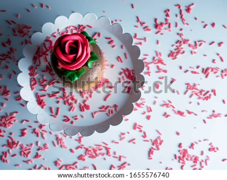 Lay flat photography picture of a yellow cupcake decorated with chocolate frosting and a red rose on a white platter with red and pink sprinkles scattered all over.  Very festive for celebration!