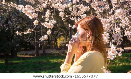 An expecting mother is sneezing while suffering from allergy to flowers and plants in spring