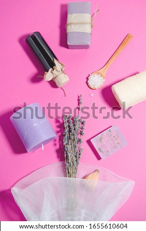 SPA accessories lie on a pink background. Lavender oil in a bottle and soap, lavender candle, salt on a wooden spoon, loofah sponge, bag with a bouquet of lavender. vertical image, flat lay