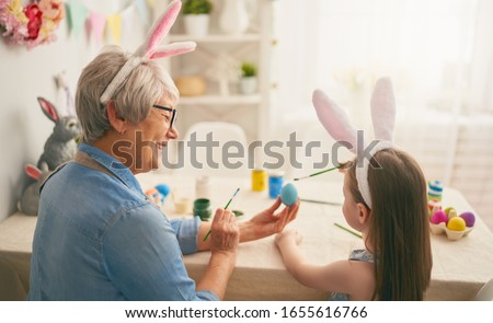 Happy easter! A grandmother and her granddaughter painting Easter eggs. Happy family preparing for Easter. Cute little child girl wearing bunny ears on Easter day.                                #1655616766