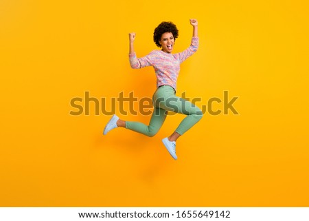 Full length photo of delighted crazy athlete afro american girl jump run win marathon raise fists scream yes wear green colorful pants trousers shoes isolated over yellow color background