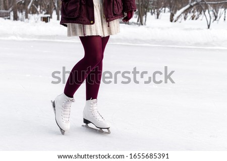 Close-up of women's legs on skates in winter on an open skating rink. Winter time. Place for text