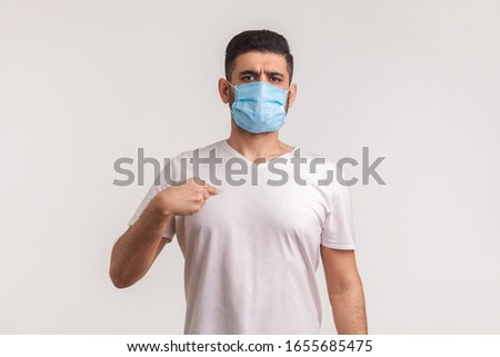 Man in surgical mask pointing himself, wearing protective filter to prevent coronavirus infection, airborne respiratory illness such as flu, 2019-nCoV, ebola. studio shot isolated on white background #1655685475