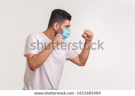 Side view of man in surgical mask punching, boxing with clenched fists, fighting against contagious disease, coronavirus infection, respiratory illness such as flu, 2019-nCoV. studio shot, isolated #1655685484