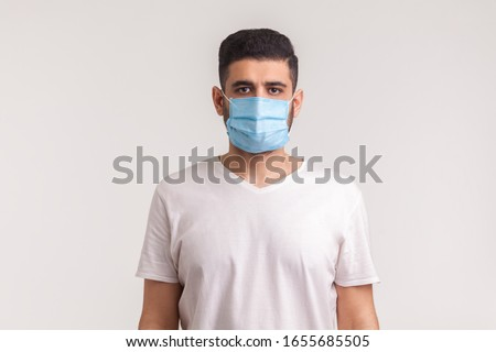 Protection against contagious disease, coronavirus. Man wearing hygienic mask to prevent infection, airborne respiratory illness such as flu, 2019-nCoV. indoor studio shot isolated on white background #1655685505
