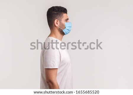 Side view of man wearing hygienic mask to prevent infection, respiratory illnesses such as flu, 2019-nCoV. indoor shot isolated, copy space for advertise about coronavirus, Covid-19prevention awarenes Royalty-Free Stock Photo #1655685520