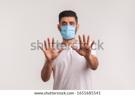 Alarming scared panicking man in hygienic mask gesturing stop, afraid of coronavirus infection, respiratory illnesses such as flu, 2019-nCoV, Covid-19, ebola. indoor shot isolated on white background #1655685541