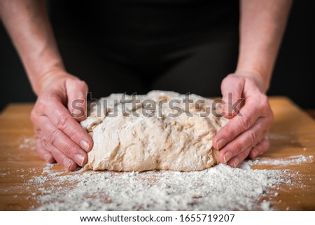 hands knead the dough on a wooden Board on the table. suitable for pizza pies pasta #1655719207