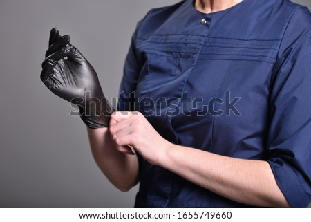 Young woman puts on black latex gloves before procedures. Close-up #1655749660