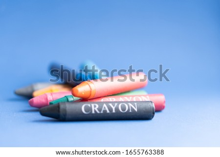 Colored crayons on a blue background. Crayons shot form above with. Colored crayons lie on a pile on a blue classic background #1655763388