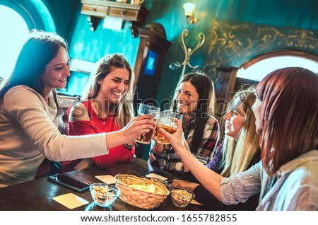 Happy girlfriends toasting beer at brewery bar restaurant - Female friendship concept with young women having genuine fun together at cool vintage pub - High iso filtered image with focus on glasses
