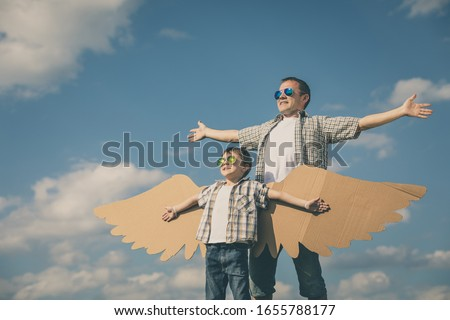 Father and son playing with cardboard toy wings in the park at the day time. Concept of friendly family. People having fun outdoors. Picture made on the background of blue sky.