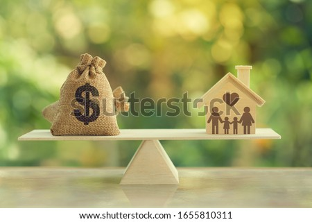 House mortgage and family financial management concept:  Wooden home and heart, Family member and US dollar hessian bags on balance scale. Prepare expenses for the purchase of a residence. #1655810311