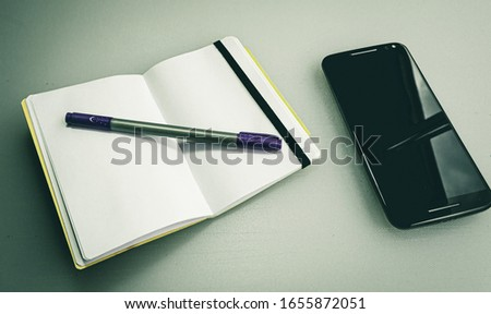 A closeup shot of a notebook with a grey and purple pen on it next to a phone #1655872051