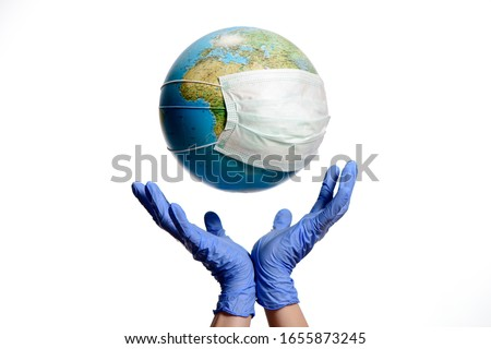 World Epidemic Danger. World need protect the earth globe with a face mask and hands, isolated on a white background. Human Epidemic Danger. Earth globe with Hungarian text.  Royalty-Free Stock Photo #1655873245