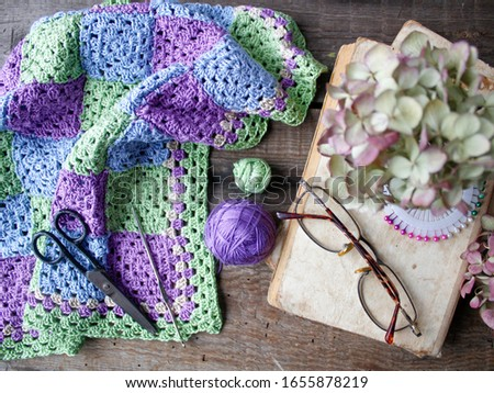 Crocheted element of green, purple, blue, beige flowers on an old wooden natural background. Screensaver for the desktop. Needlework, handmade, hobbies, free time.