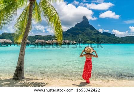 Luxury beach vacation travel destination tourist woman walking on Bora Bora island enjoying holiday in Tahiti, French Polynesia with Mount Otemanu and overwater bungalows villas hotel landscape. #1655942422