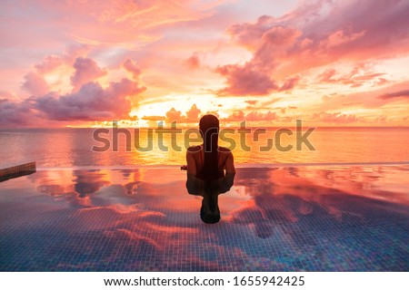 Paradise luxury resort honeymoon getaway destination at idyllic Caribbean tropical landscape hotel, woman silhouette swimming in infinity pool watching sunset serene. Winter getaway at dusk. #1655942425