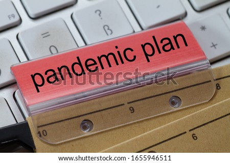 The words  pandemic plan can be seen on the label of a brown hanging folder. The hanging folder is on a computer keyboard. #1655946511