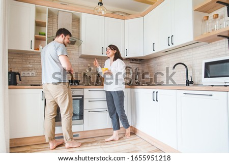 couple talking at the kitchen. man cooking breakfast #1655951218