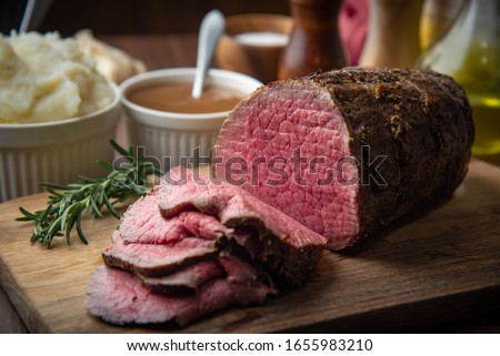 sliced eye of round beef roasted beef on cutting board Royalty-Free Stock Photo #1655983210