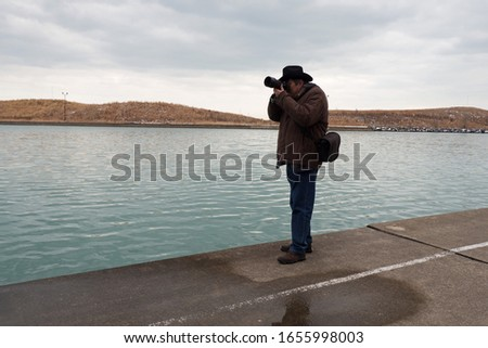 Male photographer taking pictures of  Lake Michigan in Chicago