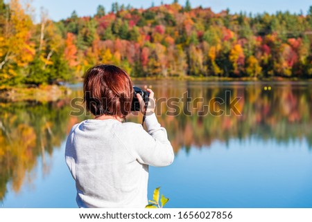 Woman photographer taking photos of a beautiful lake surrounded by a colourful autumnal forest on a sunny morning