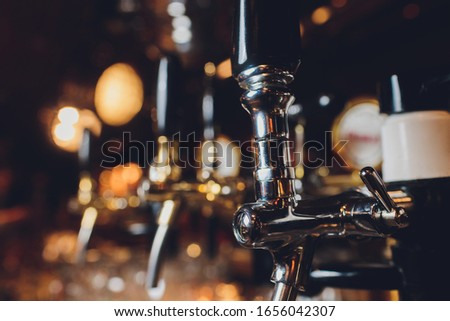 The bar counter with bottles and apparatus for dispensing beer. Apparatus for dispensing beer at the bar. Pub. The bar in the restaurant. Apparatus for dispensing beer in a restaurant. #1656042307