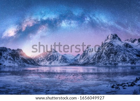 Milky Way above frozen sea coast and snow covered mountains in winter at night in Lofoten Islands, Norway. Arctic landscape with blue starry sky,  water, ice, snowy rocks, milky way. Space and galaxy Royalty-Free Stock Photo #1656049927