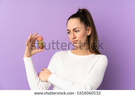Young brunette woman over isolated purple background holding colorful French macarons with sad expression #1656060532