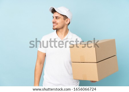 Delivery caucasian man isolated on blue background laughing #1656066724