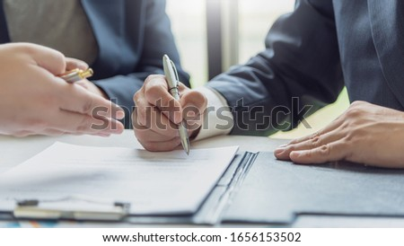 Business people signing a contract to buy or sell real estate.
