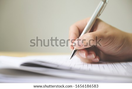 Hand of man signing signature filling in application form document Royalty-Free Stock Photo #1656186583