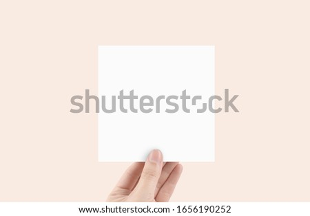 Blank Square Paper with hand mock up Royalty-Free Stock Photo #1656190252