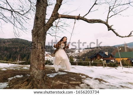 a cheerful and cheerful girl swinging on a swing on her wedding day. #1656203734