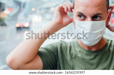 Man who puts a mask on his face. Virus concept #1656219397