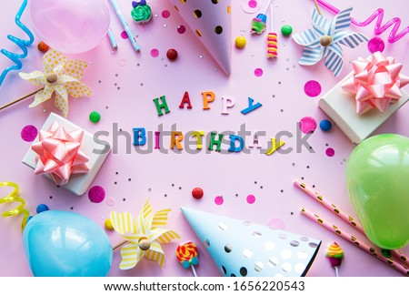 Text Happy Birthday by wooden  letters with birthday asseccories, candles and confetti  on pink background