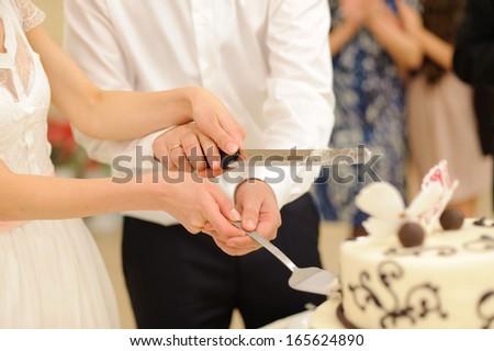 newlyweds holding knife for cake #165624890