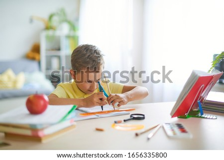 Capable boy, enthusiastically drawing a geometric shape with a compass, circle. Doing your math homework at home at your Desk. On the table are school supplies. Concentration on the geometry task.