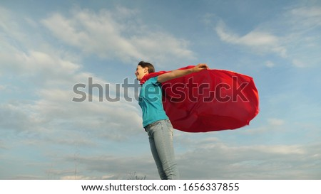 child plays in a red coat, dream of becoming a hero Superwoman. beautiful girl superhero standing on field in red cloak, cloak fluttering in the wind. Slow motion. girl dreams of becoming a superhero. #1656337855