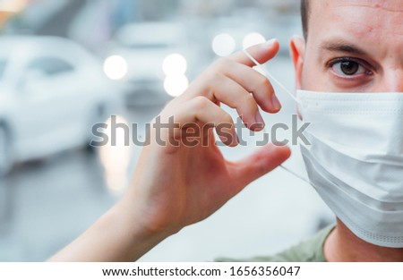 Man who puts a mask on his face. Virus concept #1656356047
