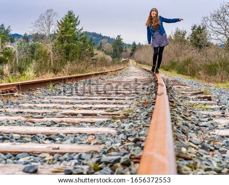 Girl balancing on old train track rail during afternoon walk on overcast day - slight movement blur - E&N Railroad in View Royal in Greater Victoria, Vancouver Island, Canada #1656372553