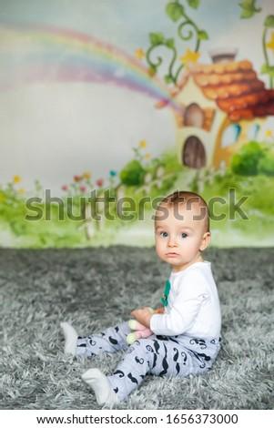First birthday cute baby boy, St. Patrick's Day theme. Cartoon fairy house on background