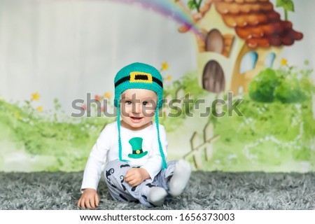 First birthday cute baby boy wearing a St. Patrick's Day hat. Cartoon fairy house on background