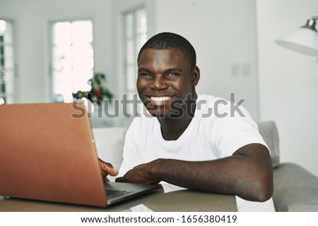 A waxed African appearance smiles at the camera and laptop on the table #1656380419