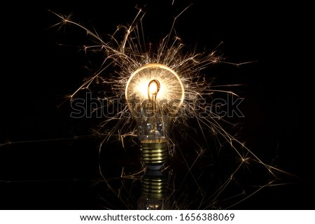 Sparkling vintage light bulb on black background - lightning flashes in an old light bulb - renewable energies, save electricity, waste electricity #1656388069