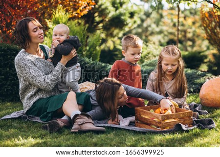 Mother with four kids having picnic on back yard #1656399925