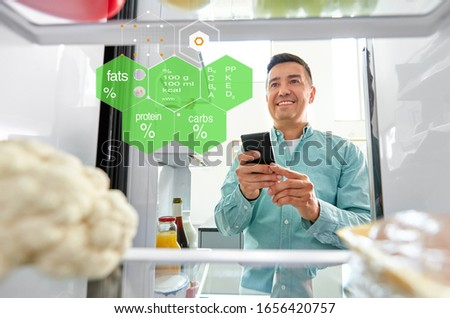 healthy eating, technology and diet concept - happy middle-aged man with smartphone at fridge at home kitchen over food nutritional value chart #1656420757