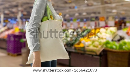 consumerism, eating and eco friendly concept - woman with white reusable canvas bag for food shopping over supermarket on background #1656421093